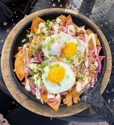absolutely perfect chicken tinga chilaquiles 💥 tortilla chips covered in shredded chicken, avo, crema, picked onions and sunny side up eggs