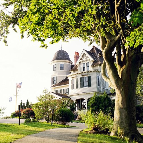 "Sure, everyone thinks of Newport as a summer destination, but @castlehillinn sports the romantic early autumn coziness we all begin to crave this time of year. The shingled 19th century mansion, complete with a turret and hunter green shutters, sits on a hill overlooking Newport Harbor and comes with kind of quriky ""formerly-owned-by-an-eccentric-Harvard-marine-biologist"" backstory essential to any good inn. Foggy drives through winding tree tunnels and autumn waves crashing over craggy cliffs will make you feel like you've been dropped into a du Maurier novel — all the more reason to book a mahogany paneled room with a fireplace to watch the Rebecca remake coming to Netflix in October. So leave leaf peeping to the amateurs, fall looks best from an adirondack chair on the lawn, old fashioned in hand. #WeMakeTravelBetter"