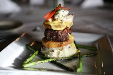 Cafe 123's Beef Tenderloin Napoleon. A 4 oz. petite filet served with fried green tomatoes, Bearnaise sauce, jumbo blue crab, chive smashed potatoes, & grilled asparagus. Located in the historic Haynie's Drugstore building in downtown Opelika, Cafe 123 features Southern cuisine with French influence. The atmosphere is laid back and luxurious, perfect for a romantic date. #auburnopelika #100dishes